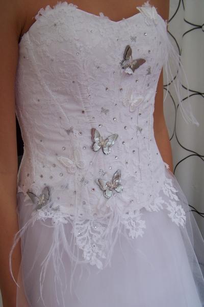 Bustier en dentelle de Calais, avec applications de strass, motifs papillon et plumes d'autruche. Jupe asymétrique en tulle.