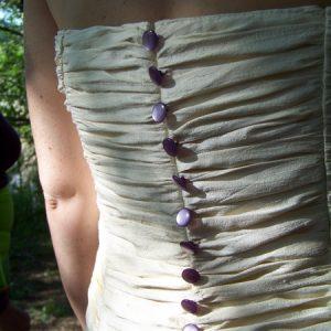 Robe de mariée en doupion de soie ivoire, ouverte sur jupon en organza de soie violet, ornée de dentelle violette (détail dos)