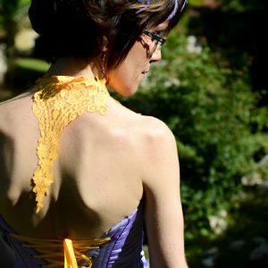 Bustier en taffetas violet avec coutures rehaussées de galon violet foncé et laçage jaune. La dentelle jaune se prolonge en tour de cou et retombe dans le dos. Accessoire cheveux assorti.