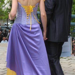Bustier en taffetas violet orné de dentelle jaune, avec coutures rehaussées d'un galon violet foncé et laçage jaune. Jupe en satin violet drapé sur satin jaune.