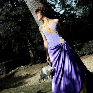 Bustier en taffetas violet orné de dentelle jaune, avec coutures rehaussées d'un galon violet foncé.  Jupe en satin violet drapé sur satin jaune.