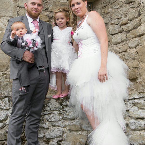 Alicia dans sa robe de mariée blanche avec des touches de rose et de gris.