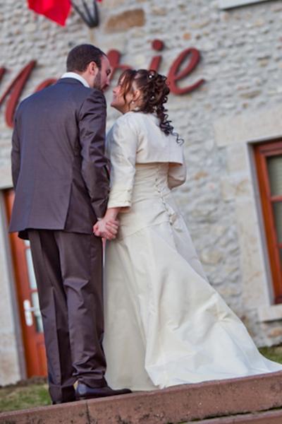 Robe de mariée en taffetas ivoire, haut drapé et orné de dentelle corail, boléro assorti