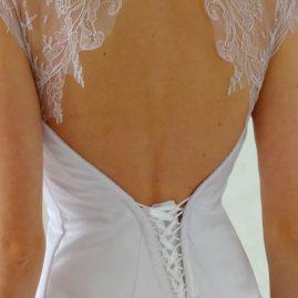 Robe de mariée en satin blanc, ornée de dentelle de Chantilly, avec grande traîne (détail dos)